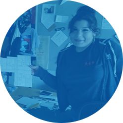 An X3 student intern holding up a project in an office