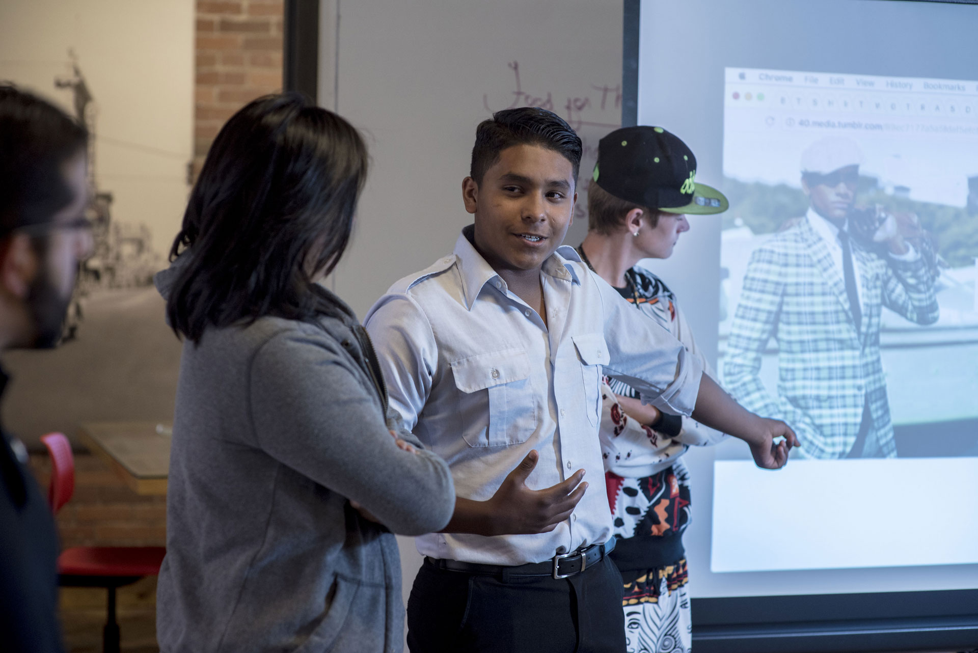 Students presenting in front of a projector screen