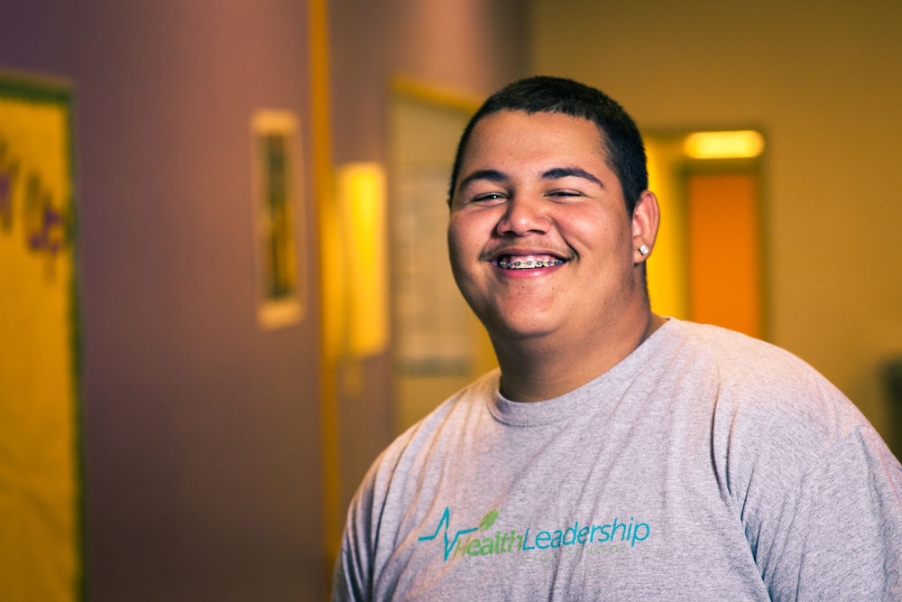 A smiling student wearing a Health Leadership High School shirt