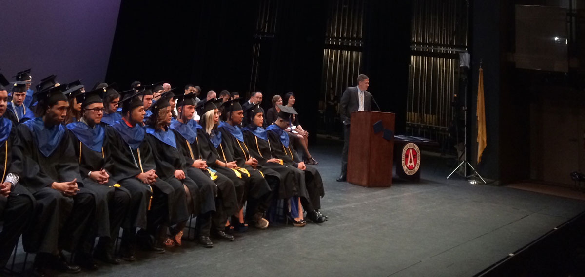 Students on stage for graduation in cap & gowns.