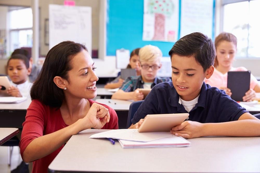 Female teacher kneeling next to male student sitting at desk