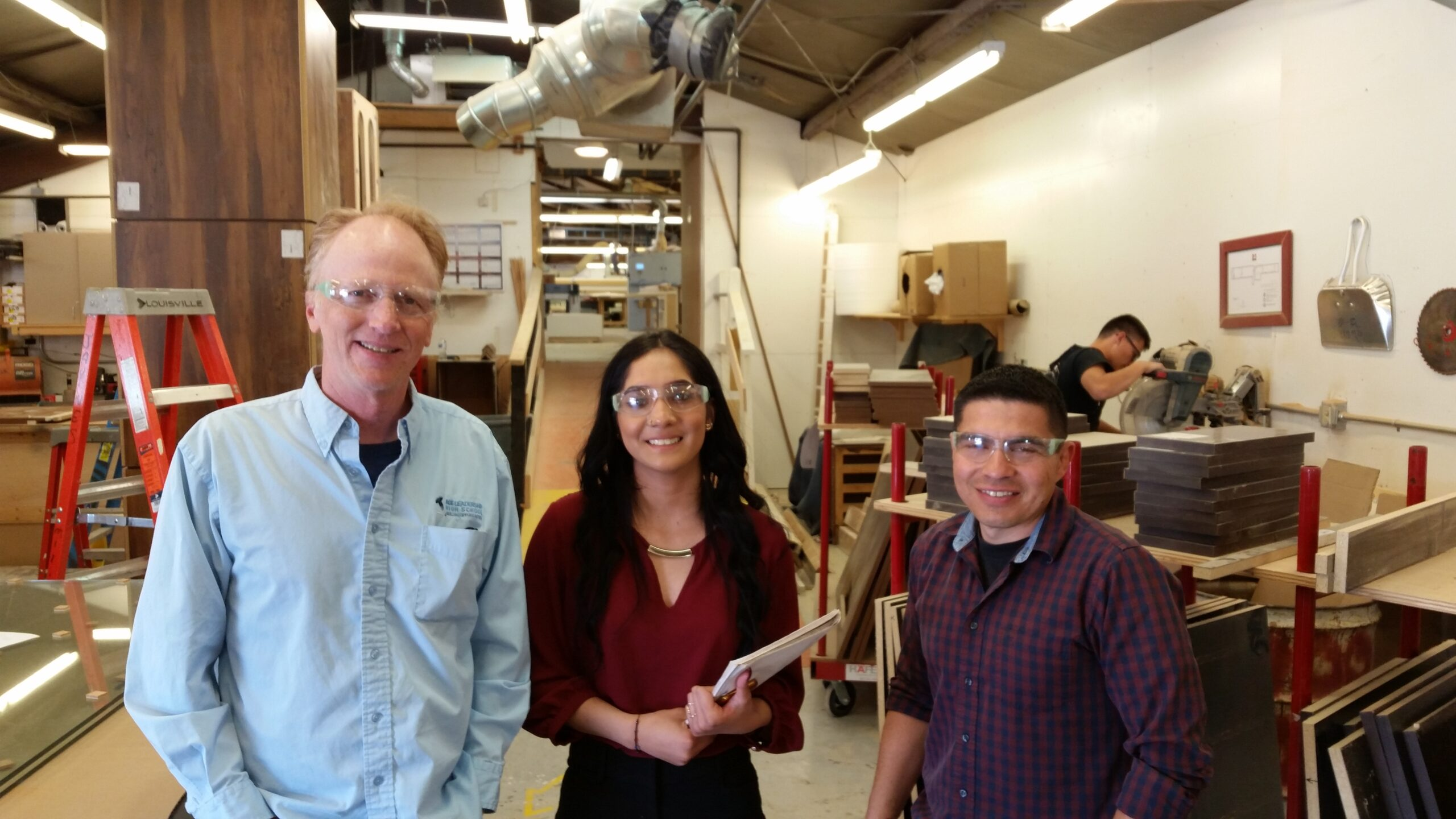 a student stands with her two adult mentors in a workshop, all three wear protective eye wear and hold clipboards